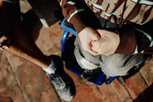 Photo showing joined hands of a wheelchair user