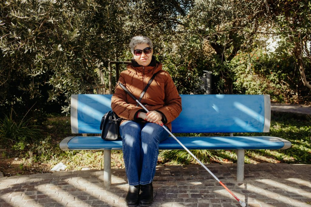 Photo of Ms. Bridget Micallef with white cane sitting on a bench