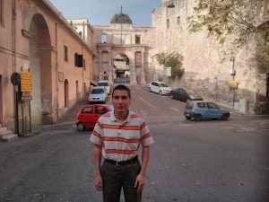 Photo of Mr. Alastair Farrugia, standing in a parking area and looking at camera